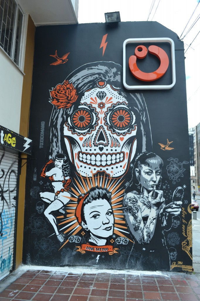 Mural of day of the dead sugar skull design in bogota with black, orange and white paint, bottom of image includes Bettie Paige and other women. Mural for Love Tattoo, Bogota.