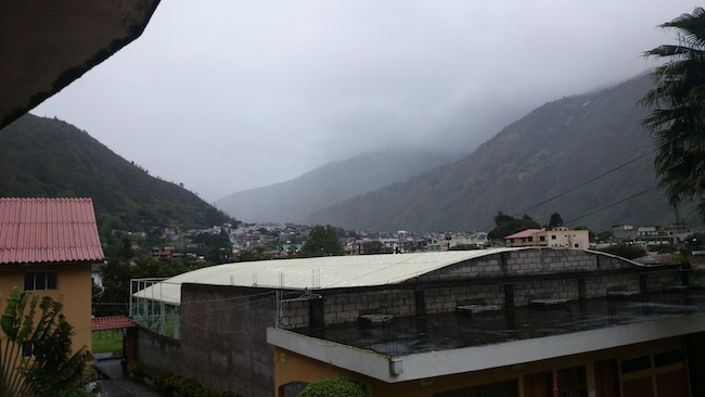 Photo of Baños, Ecuador with clouds and mist hiding the mountains in the distance.