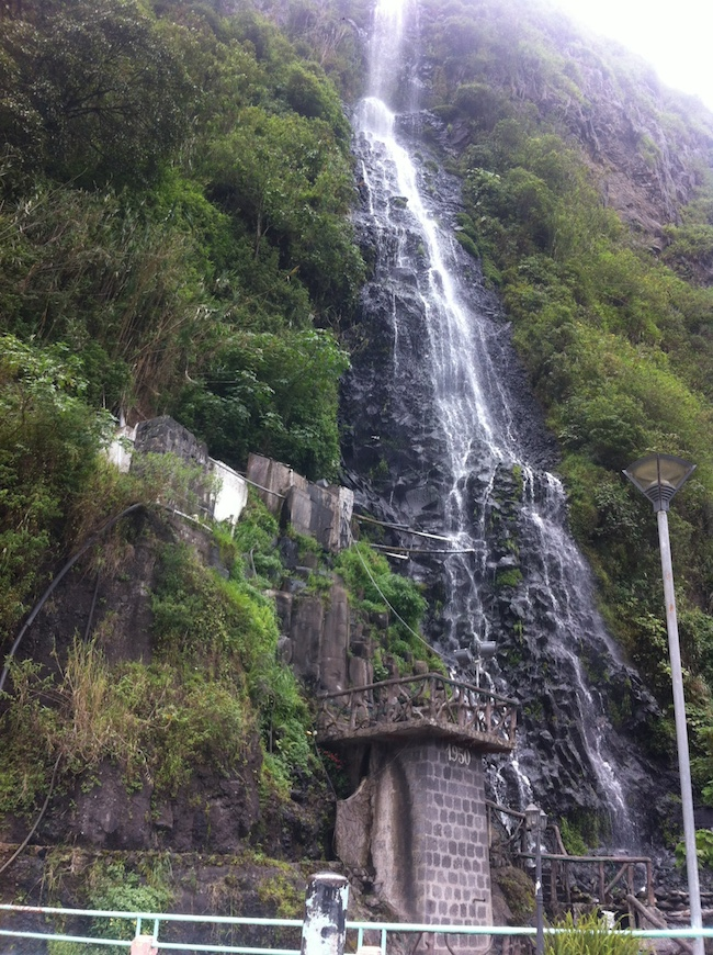 120 foot waterfall falling between green, foliage-covered mountainside in Banos, Ecuador