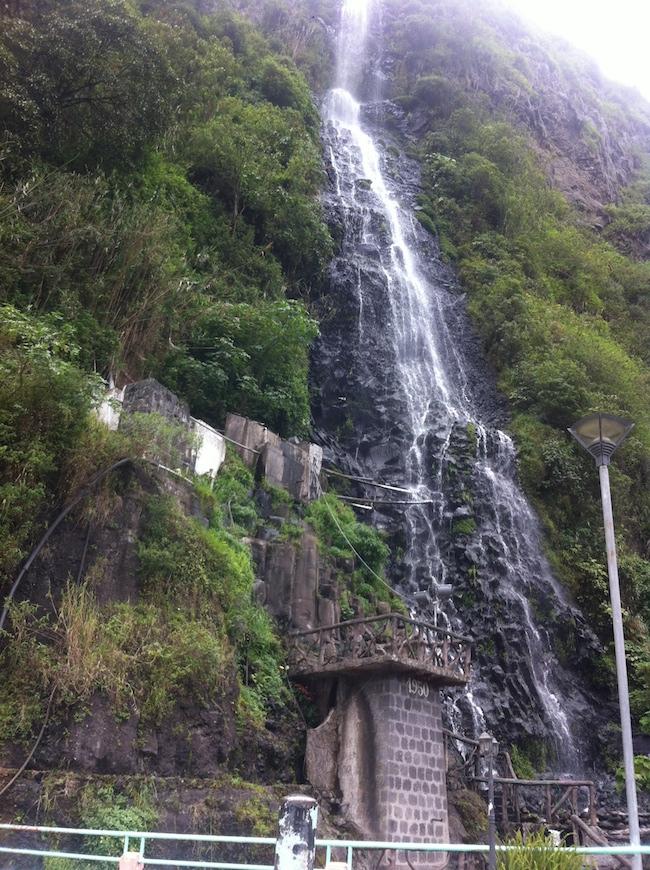 120 foot waterfall falling between green, foliage-covered mountainside in Banos, Ecuador