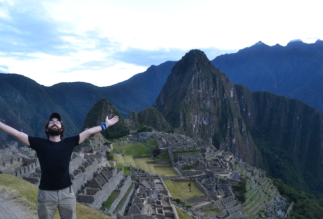Silly-looking man with arms outstretched in front of the same Machu Picchu photo everyone takes, ruined city in the mountains with green courtyards.