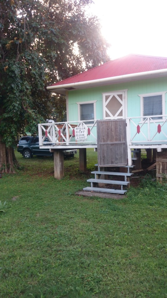 Green clapboard house on short stilts in Roatan, Honduras with red roof and white railing around front porch. Our home.