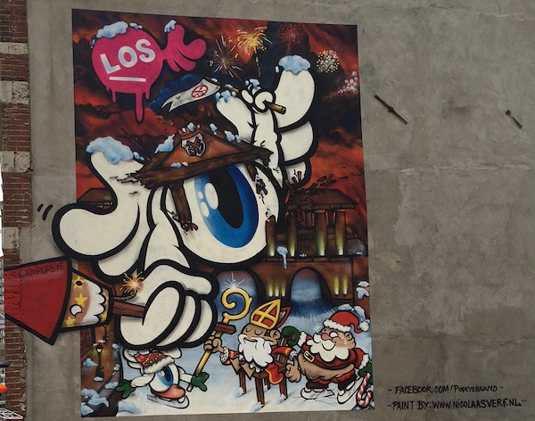 Mural in Leiden, Netherlands with a giant eyeball and tiny santa clause and bishop.